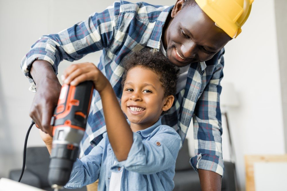 Boy enjoying helping his dad with drill